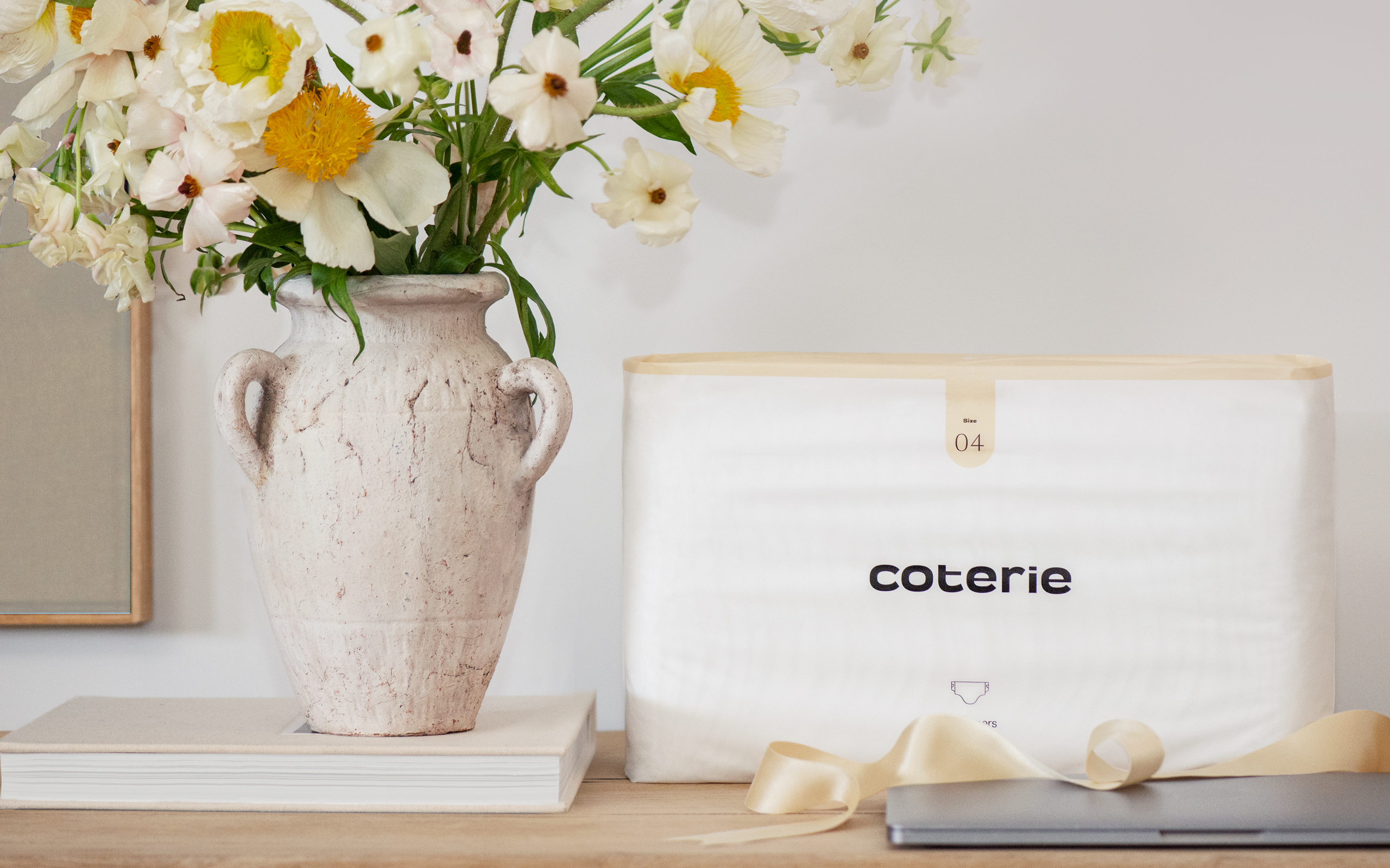 A pack of Coterie diapers next to a vase of flowers