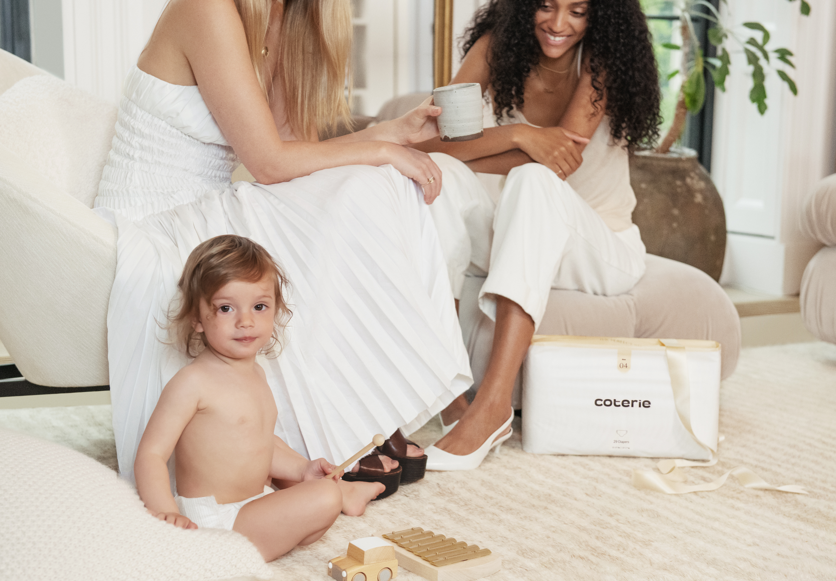 Mom's sipping coffee with their baby and a pack of Coterie diapers